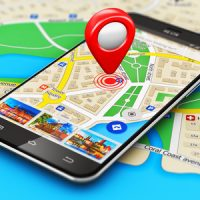 35483452 - creative abstract gps satellite navigation, travel, tourism and location route planning business concept: macro view of modern black glossy touchscreen smartphone or mobile phone with wireless navigator map service internet application on screen and red d